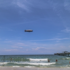From afar. All heads turn to watch the Blimp go by, over the ocean, near Pompano Beach, Florida