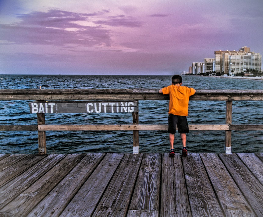 Bait cutting boy in orange