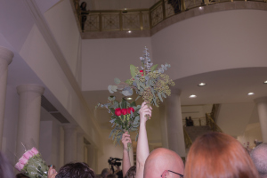 Couples raising roses in celebration